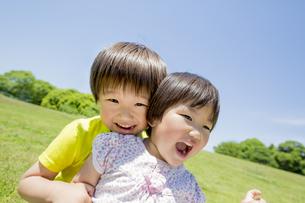 新緑の公園で遊ぶ兄と妹の素材 [FYI01075628]