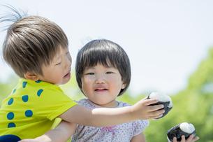 新緑の公園でおにぎりを食べる兄と妹の素材 [FYI01075631]