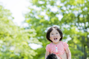 新緑の公園で父親に抱き上げられる娘の素材 [FYI01075632]