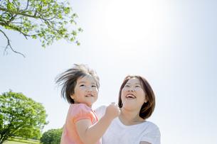 新緑の公園で母親に抱かれる娘の素材 [FYI01075637]