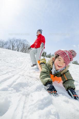 雪の公園でソリ遊びをする母と息子の素材 [FYI01075645]