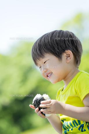 新緑の公園でおにぎりを食べる男の子の素材 [FYI01075647]