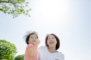新緑の公園で母親に抱かれる娘の素材 [FYI01075655]