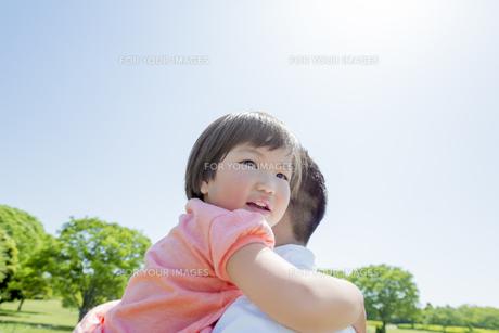 新緑の公園で父親に抱かれる娘の素材 [FYI01075658]