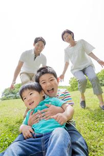 新緑の公園で遊ぶ4人家族の素材 [FYI01075660]