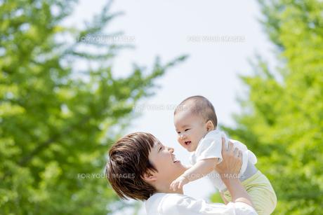 新緑の公園で母親に抱き上げられる男の子の素材 [FYI01075667]