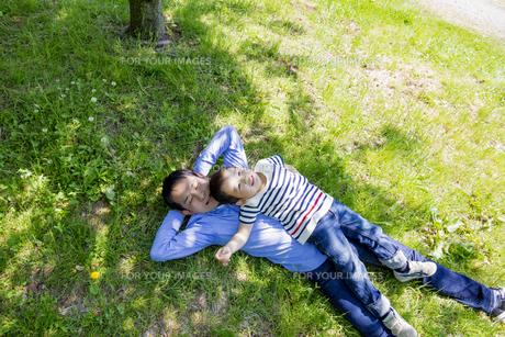 公園の木陰で横になる父親と息子の素材 [FYI01075680]