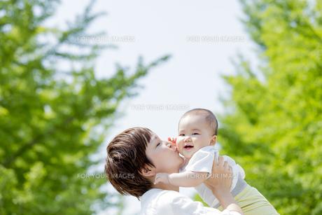 新緑の公園で母親に抱かれてキスされる男の子の素材 [FYI01075682]