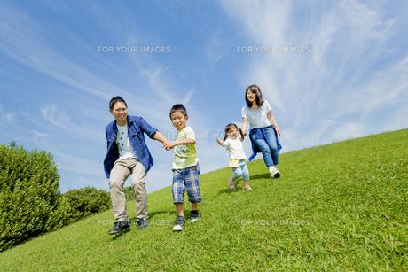 公園を手をつないで走る4人家族の素材 [FYI01075687]