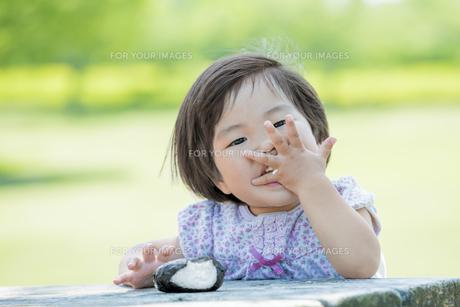 新緑の公園でおにぎりを食べる女の子の素材 [FYI01075690]