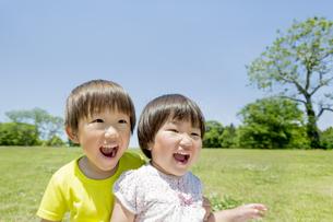 新緑の公園で遊ぶ兄と妹の素材 [FYI01075699]