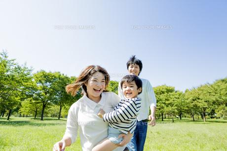 公園で息子を抱いて歩く3人家族の素材 [FYI01075706]