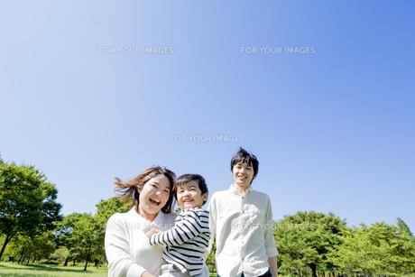 公園で息子を抱いて歩く3人家族の素材 [FYI01075707]