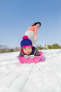 雪の公園でソリ遊びをする母と息子の素材 [FYI01075709]