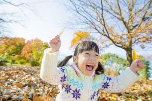 紅葉の公園で葉っぱを持って笑う女の子の素材 [FYI01075710]