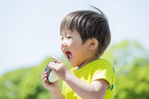 新緑の公園でおにぎりを食べる男の子の素材 [FYI01075718]