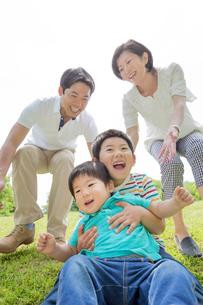 新緑の公園で遊ぶ4人家族の素材 [FYI01075723]
