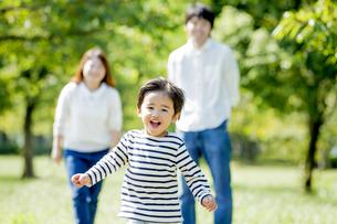 公園を走る息子を見つめる両親の素材 [FYI01075725]
