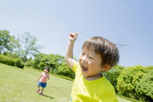 新緑の公園で遊ぶ兄と妹の素材 [FYI01075728]
