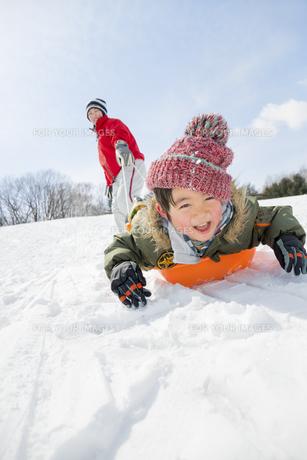 雪の公園でソリ遊びをする母と息子の素材 [FYI01075730]