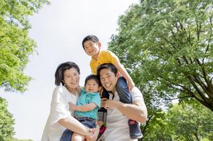新緑の公園で遊ぶ4人家族の素材 [FYI01075737]
