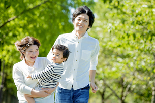 公園で息子を抱いて走る3人家族の素材 [FYI01075740]