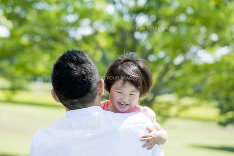 新緑の公園で父親に抱かれる娘の素材 [FYI01075741]