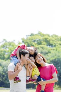 新緑の公園で遊ぶ4人家族の素材 [FYI01075745]