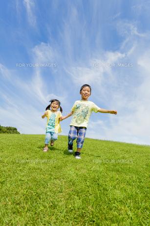 公園を手をつないで走る兄と妹の素材 [FYI01075752]