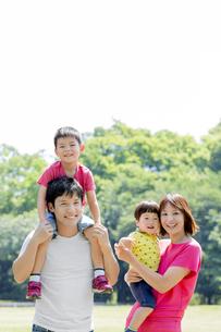 新緑の公園で遊ぶ4人家族の素材 [FYI01075755]