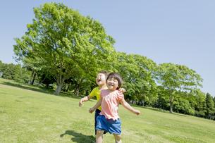 新緑の公園で遊ぶ兄と妹の素材 [FYI01075756]