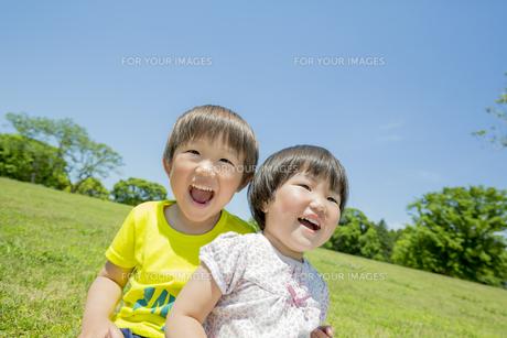 新緑の公園で遊ぶ兄と妹の素材 [FYI01075762]
