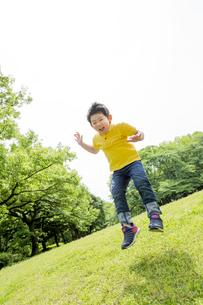新緑の公園でジャンプをする男の子の素材 [FYI01075769]