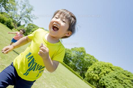新緑の公園で遊ぶ兄と妹の素材 [FYI01075775]