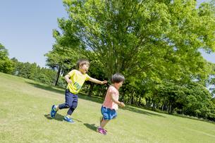新緑の公園で遊ぶ兄と妹の素材 [FYI01075802]