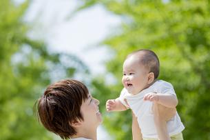新緑の公園で母親に抱き上げられる男の子の素材 [FYI01075813]