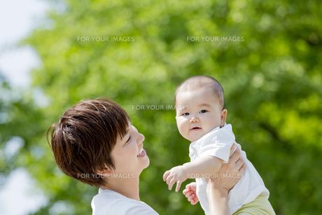 新緑の公園で息子を抱き上げる母親の素材 [FYI01075845]