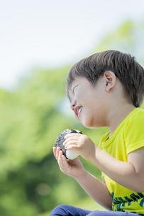 新緑の公園でおにぎりを食べる男の子の素材 [FYI01075846]