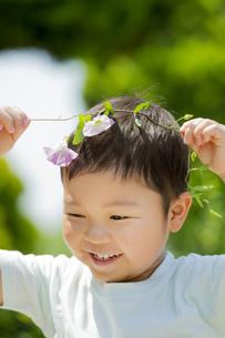 初夏の公園でヒルガオを持って笑う男の子の素材 [FYI01075850]