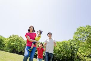 新緑の公園を歩く4人家族の素材 [FYI01075851]