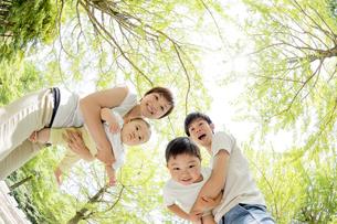 新緑の公園で遊ぶ4人家族の素材 [FYI01075860]