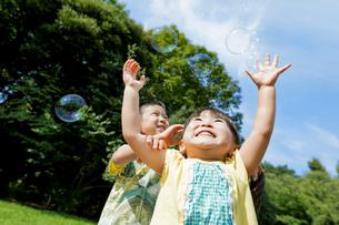 公園でシャボン玉を追う兄と妹の素材 [FYI01075862]