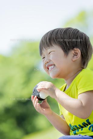 新緑の公園でおにぎりを食べる男の子の素材 [FYI01075886]
