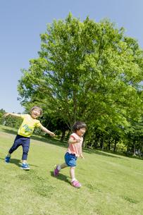新緑の公園で遊ぶ兄と妹の素材 [FYI01075897]