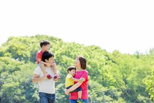 新緑の公園を歩く4人家族の素材 [FYI01075911]