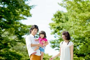 公園で娘を抱く両親の素材 [FYI01075921]