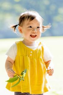 公園でドングリを持つ女の子の素材 [FYI01075924]