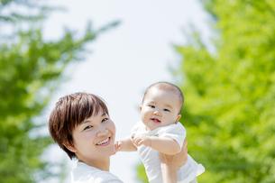 新緑の公園で母親に抱かれる男の子の素材 [FYI01075925]