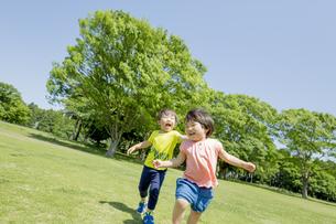 新緑の公園で遊ぶ兄と妹の素材 [FYI01075974]