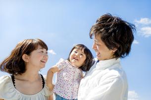 公園で娘を抱く両親の素材 [FYI01075978]